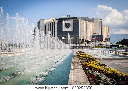 Sofia, Bulgaria. August 3, 2018. The National Palace Of Culture Seen Through The Fountain Water Jets