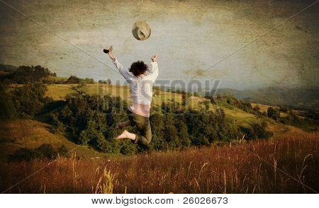 Vintage photo of woman jumping on field and throwing her hat