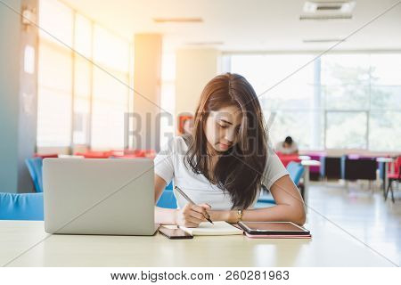 Attractive Young Asian Female College Student Studying Ebook Online Course And Writing Notes On Note