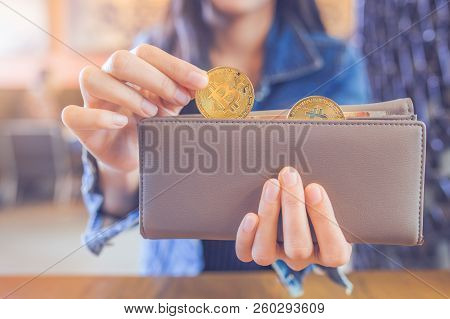 Woman Hand Is Pulling A Bitcoin Out Of A Wallet.