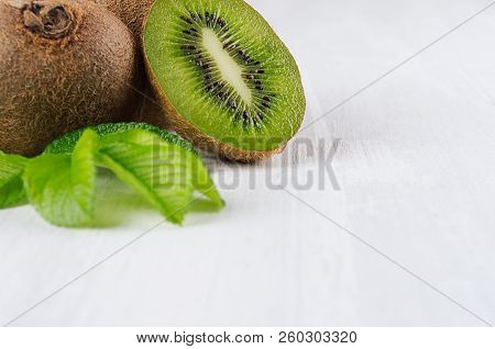 Ripe Fleshy Green Kiwi With Juicy Slice, Young Leaves On Soft Light White Table, Closeup, Top View.
