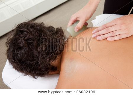 Young male receiving Gua Sha treatment on back and shoulders