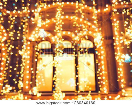 Bright Christmas Street Illumination On The Facade Of The Buildings With Windows. The City Is Decora