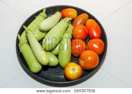 Tomatoes And Brinjal In A Black Plastic Plate