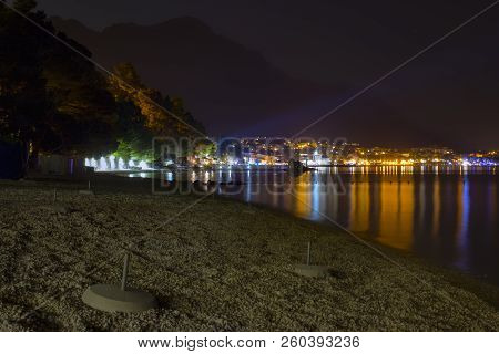 Night View Of The Illuminated Seaside Town Of Baska Voda In Croatia. In The Foreground Is A Pebble B