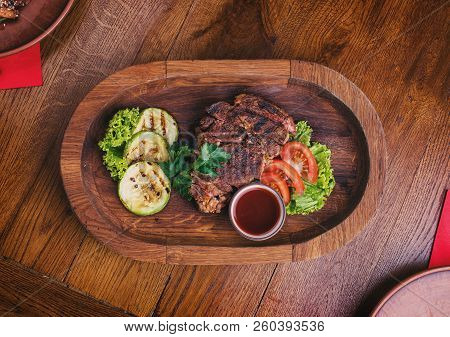 Hot Steak With Sauce And Vegetables. Snacks For Beer At The Pub