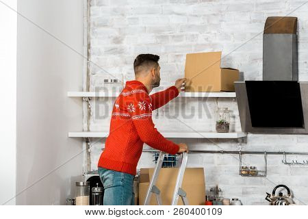rear view of man standing on ladder and putting cardboard box on shelf in kitchen during relocation in new home poster