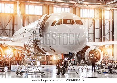 Passenger Commercial Airplane On Maintenance Of Engine Turbo Jet And Fuselage Repair In Airport Hang