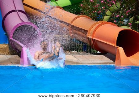 Man Having Fun In Aqua Park. He Is Sliding Down From The Attraction. Thera Are A Lot Of Splashes Aro