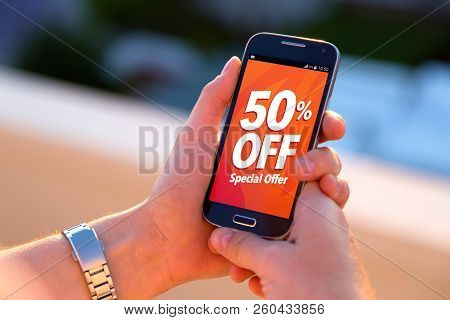 50% Off Sale. Girl Holding A Smartphone With A 50% Discount Advertising On The Screen. Marketing, Ec