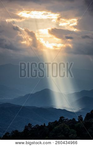 Bright Sunlight Shining Through Hole Of Clouds To Dark Scene Of Mountain Range Before Sunset In Thai