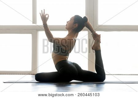 Young Woman Practicing Yoga, Doing One Legged King Pigeon Exerci