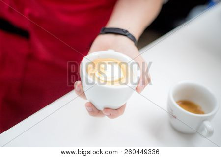 Barista Holds A Cup With A Figurative Coffee Latte In The Form Of A Heart