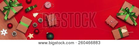 Gift Boxes, Christmas Balls, Toys, Fir Cones, Ribbon On Red Background. Festive, Congratulation, New