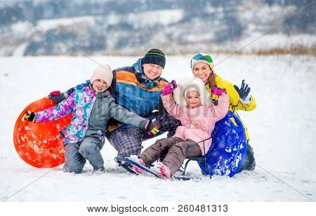 Active happy family smiling and laughing while playing outdoors during winter holidays. Winter fun outdoors with children