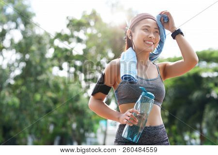 Young Happy Asian Woman In Sportswear Wiping Forehead With Towel While Smiling Away In Park