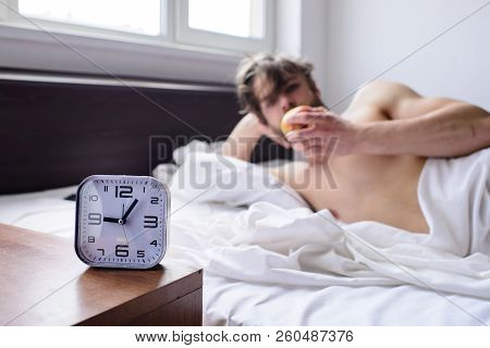 Get Up Early Morning Tips. Man Bearded Unshaven Handsome Guy Lean On Hand While Eats Fruit Near Alar