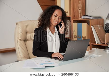 Beautiful Ethnic Businesswoman With Curls Sitting At Table In Office Speaking On Phone And Using Lap