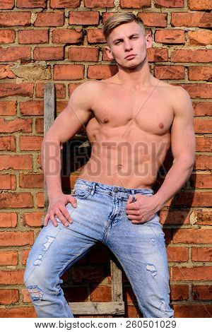 Strong muscles emphasize masculinity sexuality. Man muscular chest naked torso stand brick wall background. Attractive and confident. Sexy torso sportsman. Man muscular athlete lean on wall relaxed poster