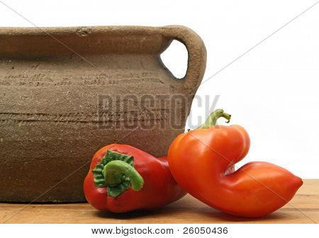 two red peppers with old clay pot