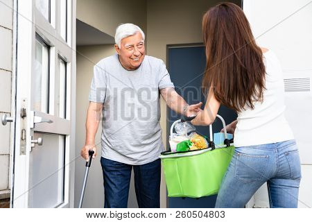 Senior Man With Walking Stick Offering Help To His Young Daughter Carrying Groceries