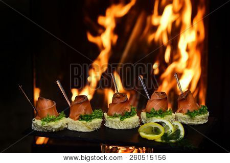 Tasty Bruschetta With Salmon On Burning Fire Background. Bruschetta Or Canapes On Taosted Baguette T
