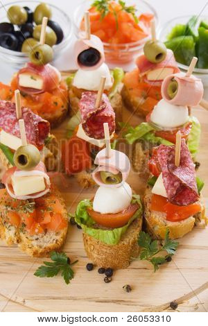 Bruschetta, italian cold buffet with tomato, olive, ham and herbs