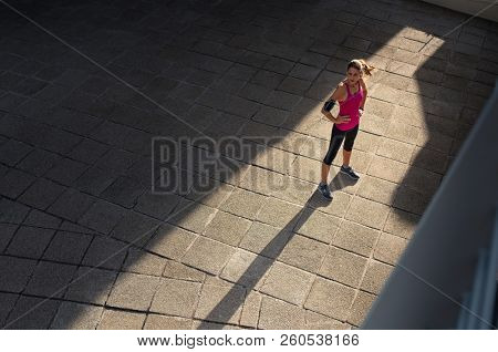 Mature woman taking a break after sport training in city street. Fitness runner relaxing after city jogging and working out outdoors. High angle view of runner standing on sidewalk with copy space.