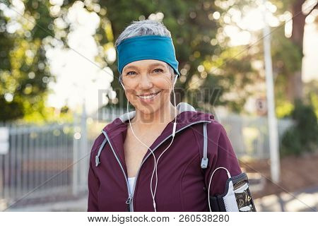 Portrait of smiling senior woman listening to music after running. Portrait of healthy mature woman wearing blue headband and sportswear. Fitness lady looking at camera after workout exercise.