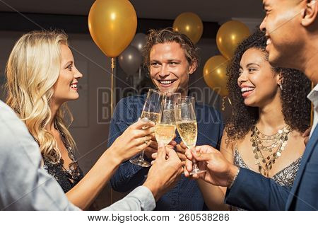 Group of young multiethnic friends toasting with champagne flutes to celebrate new year. Happy guys and girls raising their glasses for party new year's eve with golden and silver baloons.