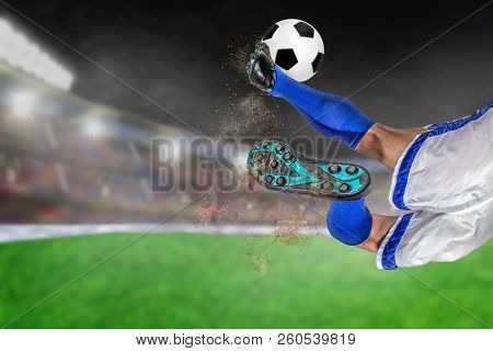Soccer Player With Spectacular Scissor Kick Of Football In Brightly Lit Outdoor Stadium. Focus On Fo