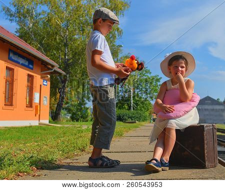 Adorable Little Girl And Boy On A Railway Station, Waiting For The Train With Vintage Suitcase. Trav