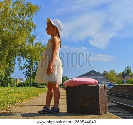 Adorable Little Girl On A Railway Station, Waiting For The Train With Vintage Suitcase. Traveling, H