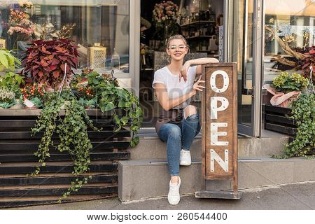 Attractive Smiling Flower Shop Owner Sitting On Stairs With Open Signboard