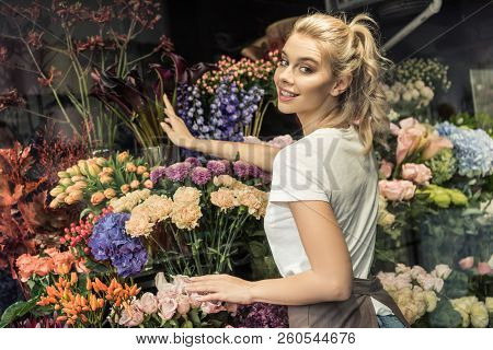 Smiling Attractive Florist Taking Care Of Flowers In Flower Shop And Looking At Camera