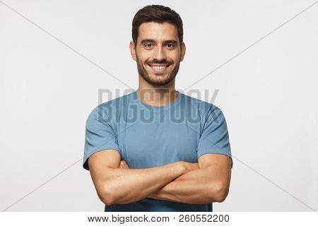 Portrait Of Smiling Handsome Man In Blue T-shirt Standing With Crossed Arms Isolated On Grey Backgro