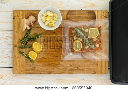 Packaged Fish Fillet Sitting Next To Vacuum Packer And Garlic Cloves Inside Small White Bowl On Top