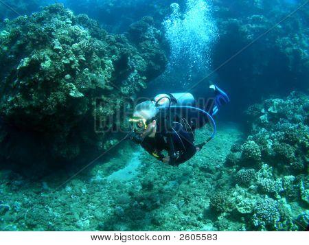 Scuba Diver Finning Through An Underwater Channel