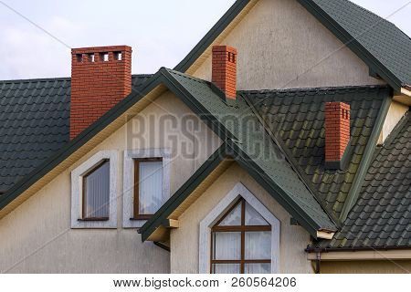 Top Of Big Modern Expensive Residential House With Shingled Green Roof, High Brick Chimneys, Stucco
