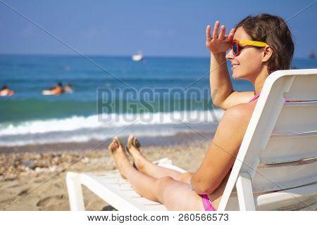 Cute Beautiful Young Woman Sunbathing On Sunbed On Sea Beach. Tanned Girl On Sea. Relax On Sea Beach