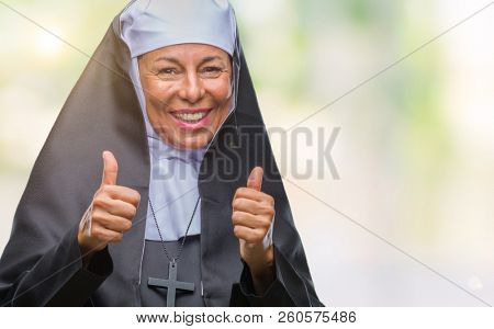 Middle age senior christian catholic nun woman over isolated background approving doing positive gesture with hand, thumbs up smiling and happy for success. Looking at the camera, winner gesture.