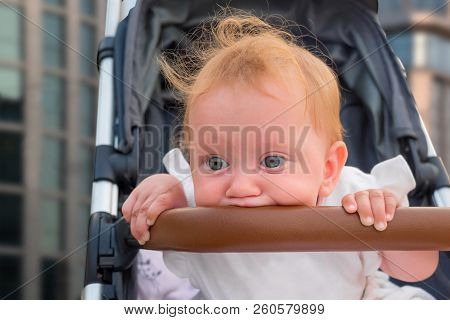 Baby Vehicles. Sitting And Waiting For Mother. Cute Baby Girl Get Bored. Kid's Hands Holding Bumper,