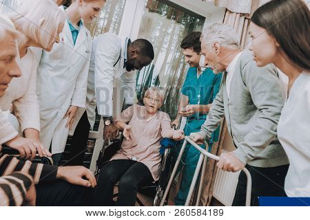 Man With Crutches. Rehabilitation. Patient On A Wheelchair. Doctor In Nursing Home. Smiling Patients
