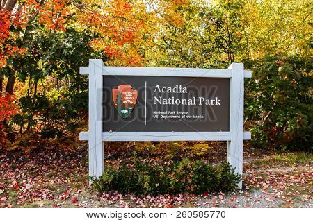 BAR HARBOR, MAINE, USA-OCTOBER12, 2016:  Acadia National Park sign with afternoon lights during Autumn season with colored leaves.