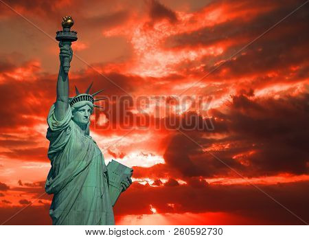 The Statue Of Liberty And Dramatic Sky At Sunrise