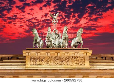 The Statues On Top Of Brandenburg Gate At Sunset In Berlin Germany