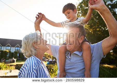 Grandparents Giving Grandson Ride On Shoulders In Summer Park Against Flaring Sun