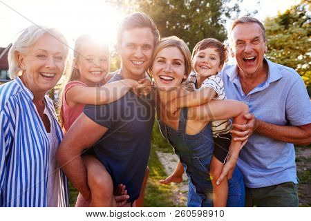 Portrait Of Smiling Multi Generation Family Outdoors In Summer Park Against Flaring Sun