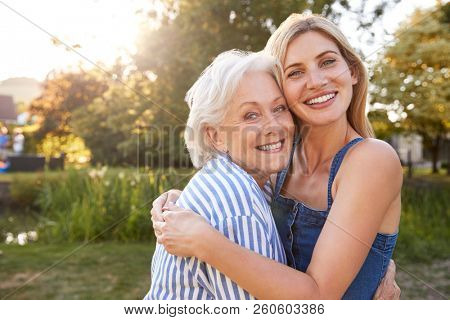 Portrait Of Smiling Mother Hugging Adult Daughter Outdoors In Summer Park