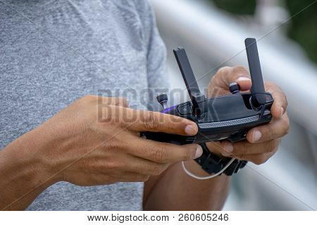 Close up of man's hands holding remote controller or ground based controller of commercial unmanned aerial vehicle (UAV) or drone for an aerial photograhy. poster